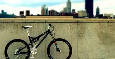 a bicycle leaned against a cement wall, the city of pittsburgh's skyscrapers rise in the background