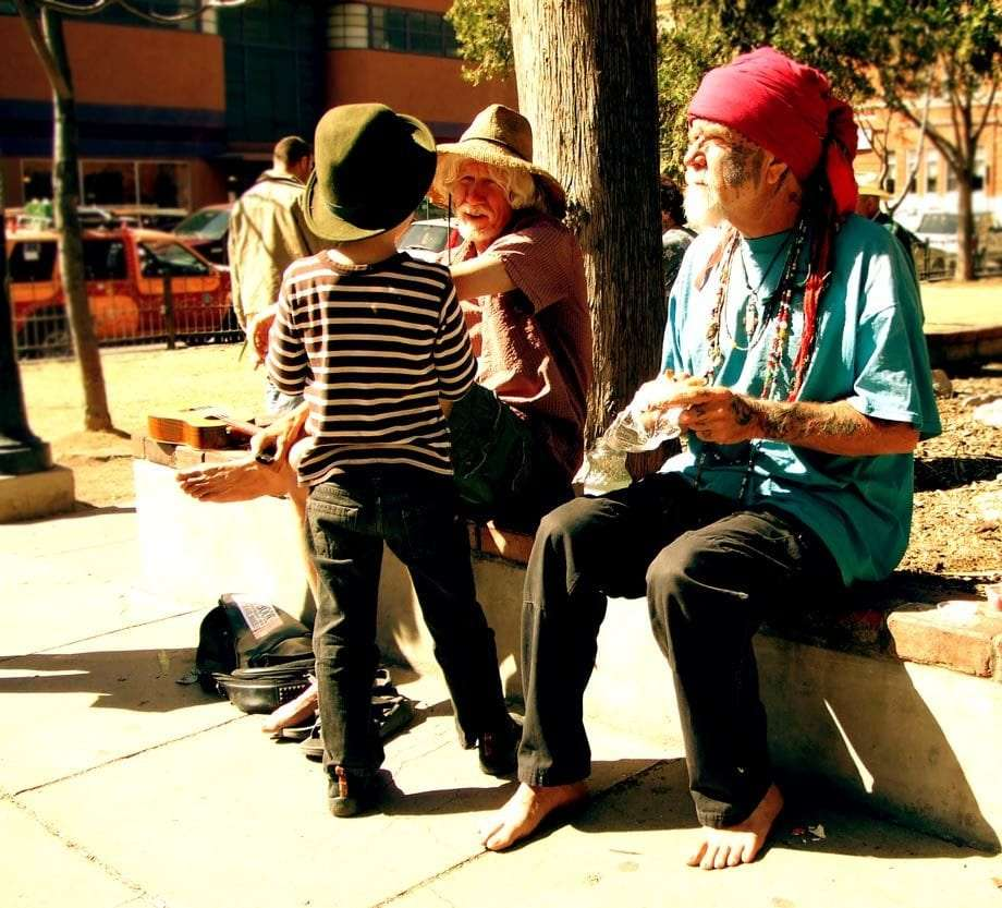 a young boy and two older men, all buskers, sit on a park wall in Bisbee, Arizona