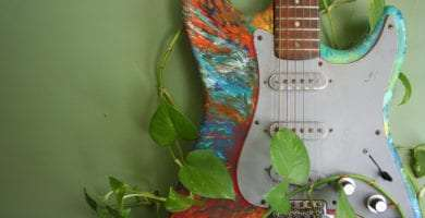 a rainbow painted guitar covered in ivy