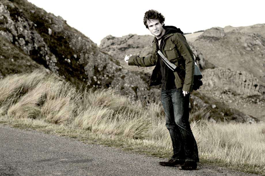 a young man wearing a green jacket and small bag hitchhiking
