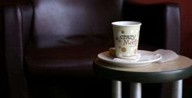 a cup of crazy mocha coffee on a small table in front of a leather chair