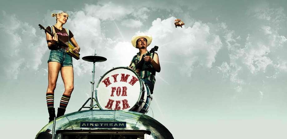two musicians perched upon the top of an Airstream, a pig flies through a partly cloudy sky behind