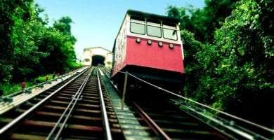 a steep track, similar to a railroad, a red car being lifted up toward a white house - an inclined plane