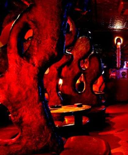 a room resembling hardened molten rock, lit red with stone tables throughout