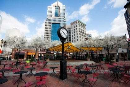 a clock rises above several chairs on a brick patio area, a skyscraper towers behind