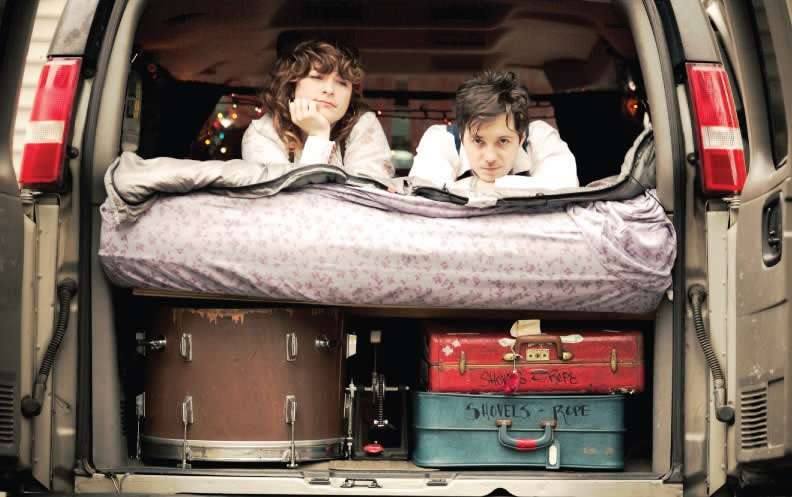 a man and woman lay in the back of an open van, there drum and suitcases stacked below