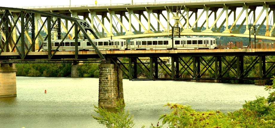 a light rail train crosses a black bridge over the Monogahela river, another yellow bridge in the background