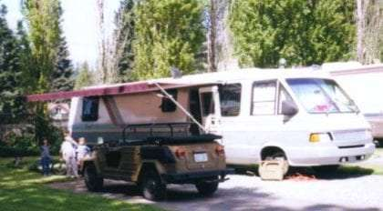 an old jeep, a Volkswagen Thing to be exact, and three children parked in front of an RV