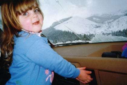 a young girl in a blue sweater warms her hands on the dashboard, snow covered mountains in the background