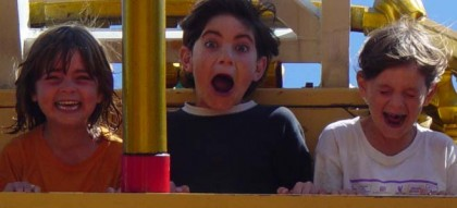 three kids screaming on a rollercoaster
