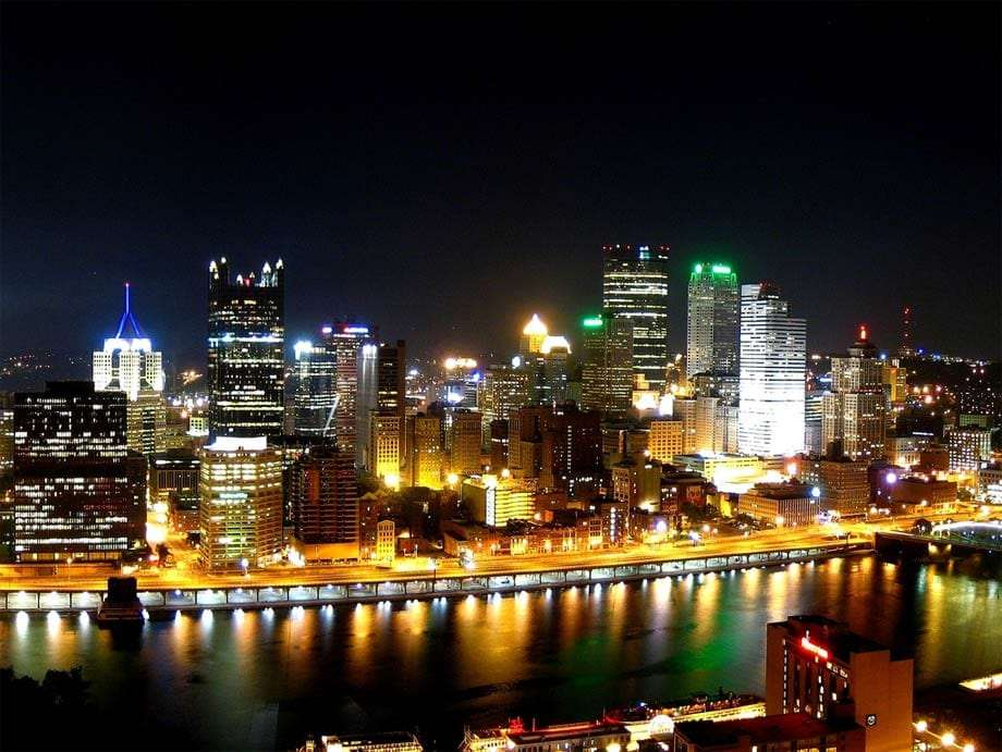 lights illuminate downtown Pittsburgh, reflected in the Monongahela River