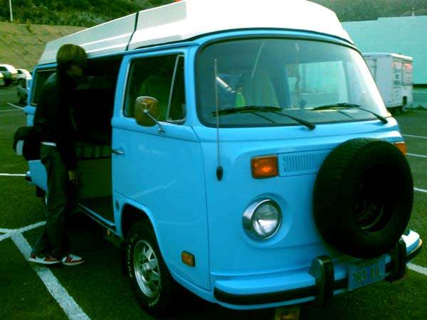 a blue 1979 volkwagen bus, a tall guy peering into the side barn door of it, happy as all hell