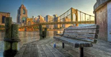 a wooden bench along the Allegheny River, the large yellow bridge and the skyline of the city of Pittsburgh rise in the background