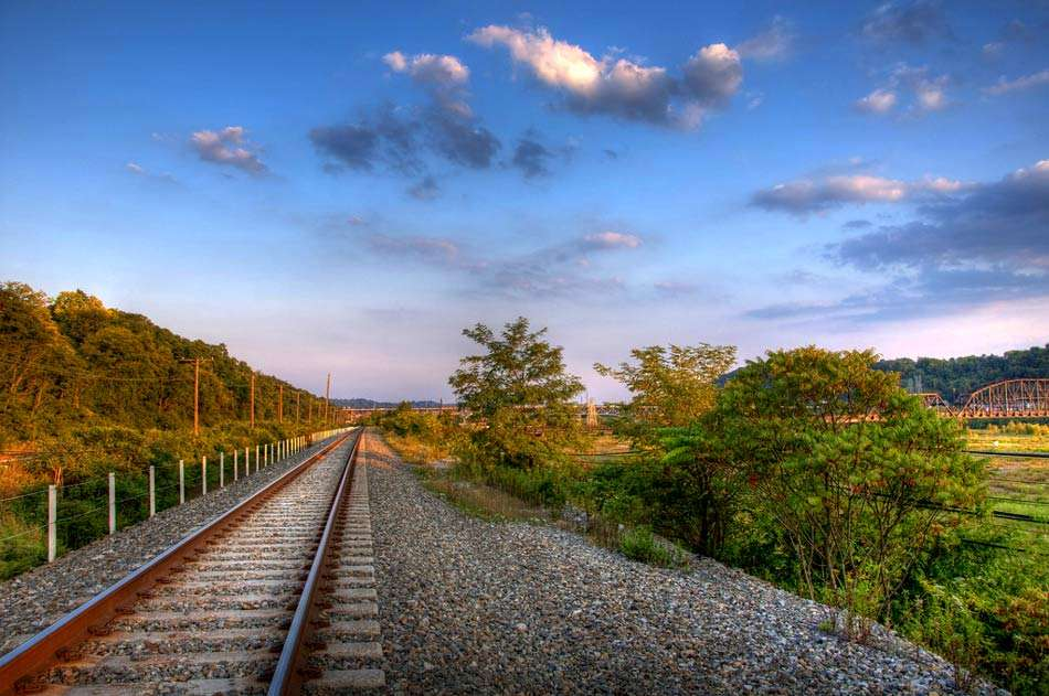 train tracks lead off into the rolling hills