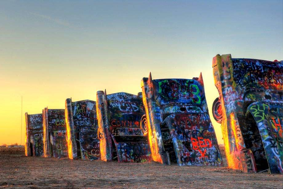 graffiti laden cadillacs, hoods down and into the ground, the desert sun sets behind