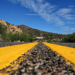 two yellow lines run down an asphalt road, the desert forest and blue sky in the background