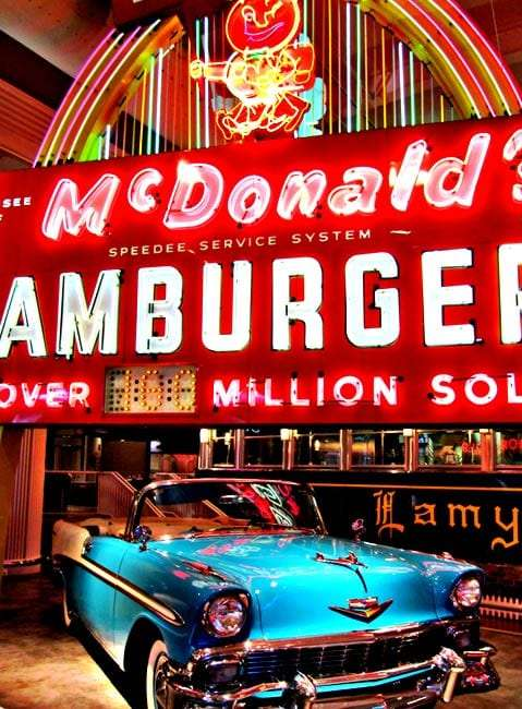 a vintage glowing red and vivid every other color neon McDonalds sign touts hamburgers and some number of million sold