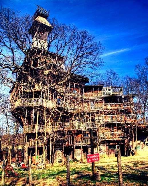 A multi-storied, mult-layered treehouse dwarfing the original tree in size