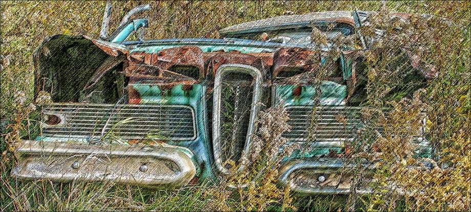 old rusted out blue car in a field