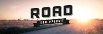 roadtrippers logo against a two lane road disappearing into the sun
