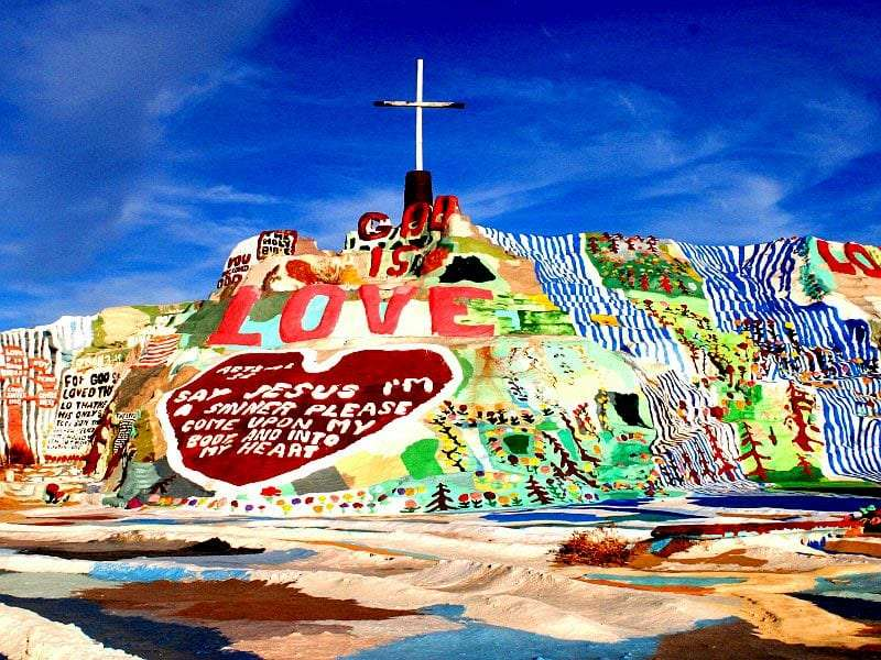 a colorful mountain made of cement and painted with murals, topped by a cross