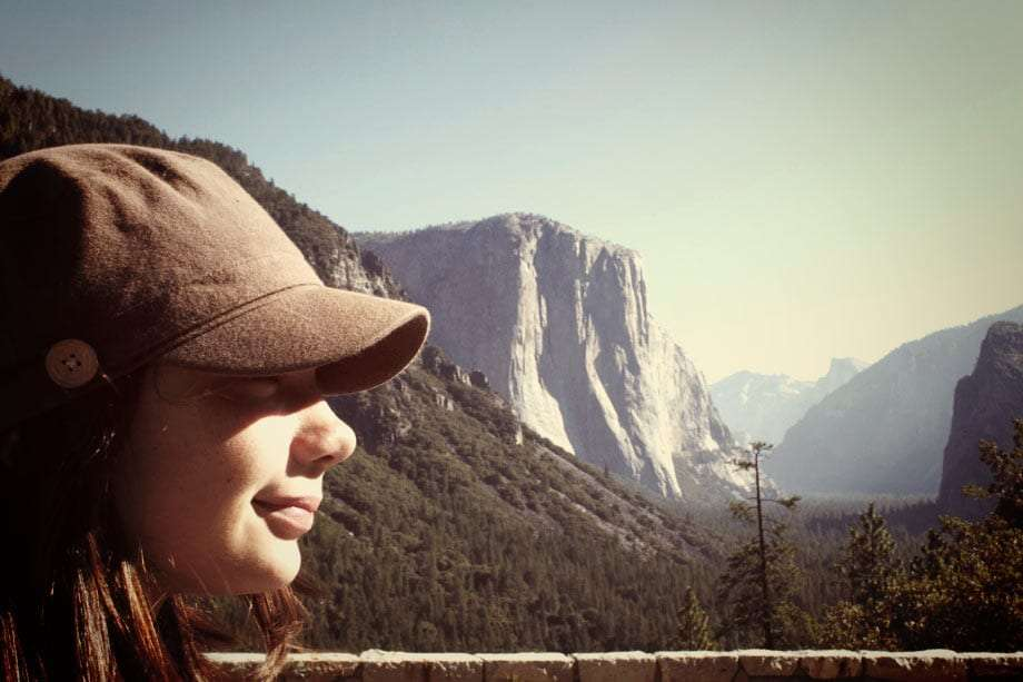 a young girl in one of those military hipster style hats, her profile against the grandest mountains of yosemite national park