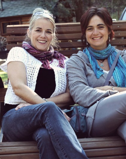 two obviously happy women, clearly friends, sitting on a park bench enjoying life