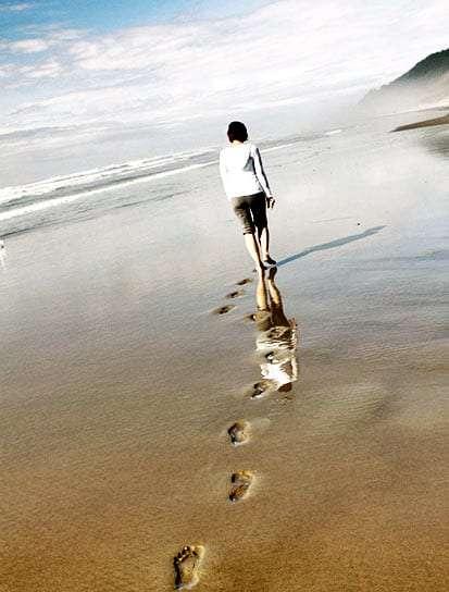 a woman walks alone through the sands of an Oregon Coast beach