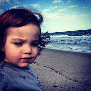 a toddler with wild hair grimaces on a beach