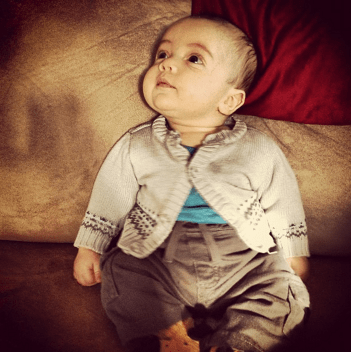 a baby dressed primarily in sepia tone sits on a couch