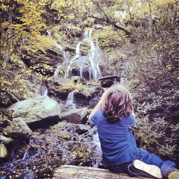 a young boy photographs a waterfall