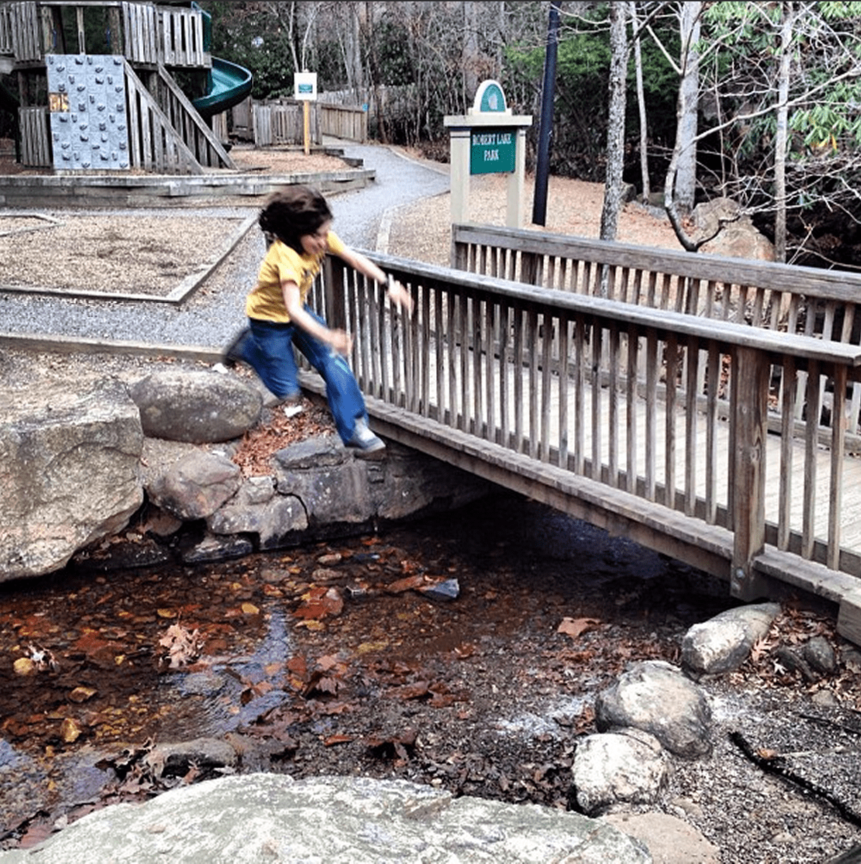 a young man jumps over a rather wide creek