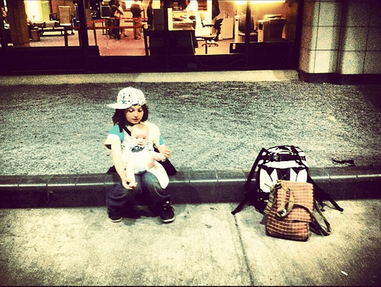 a young boy holds a baby, their luggage next to them, in front of an airport