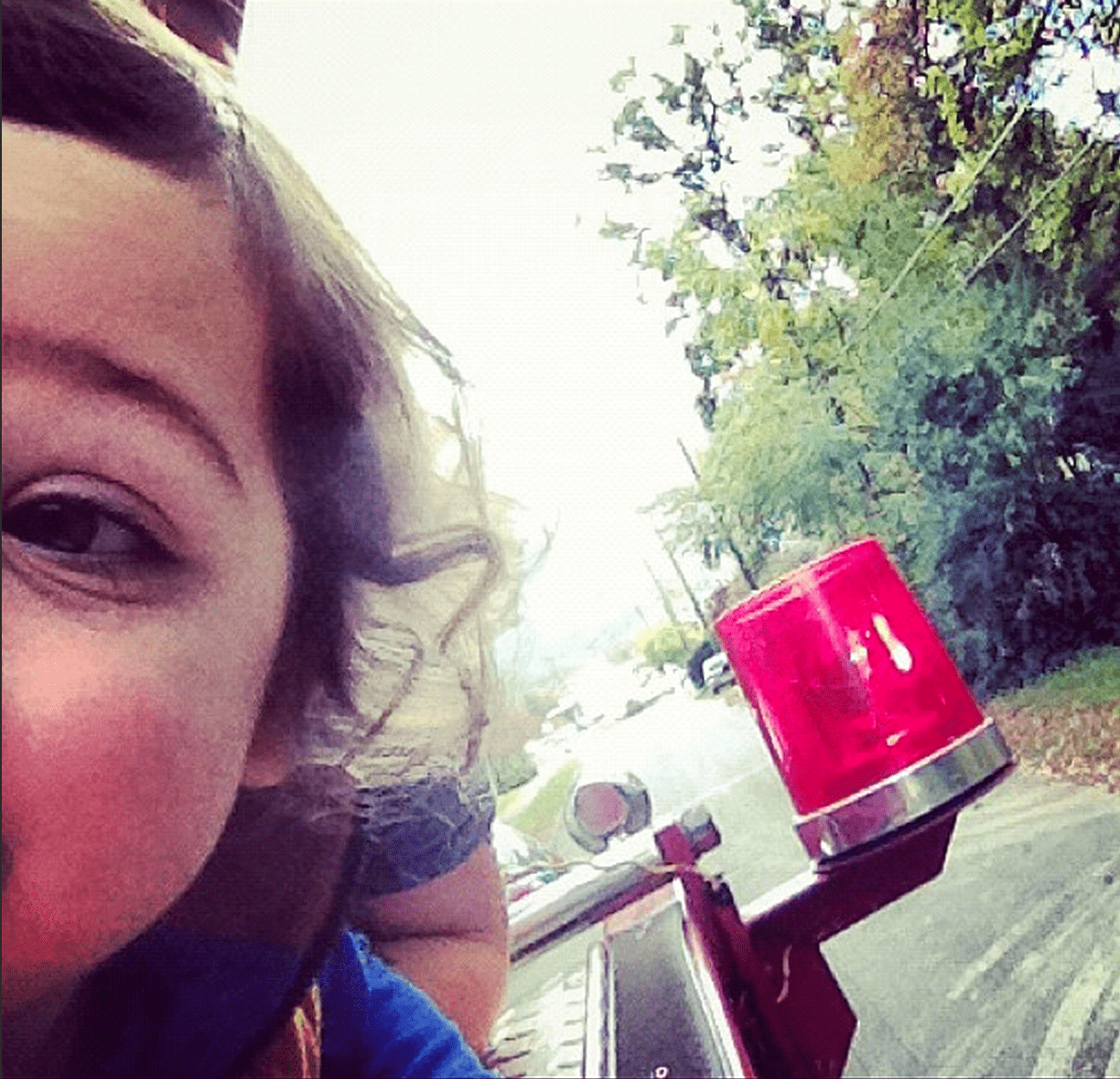 half a toddler's face can be seen, he's riding on a firetruck