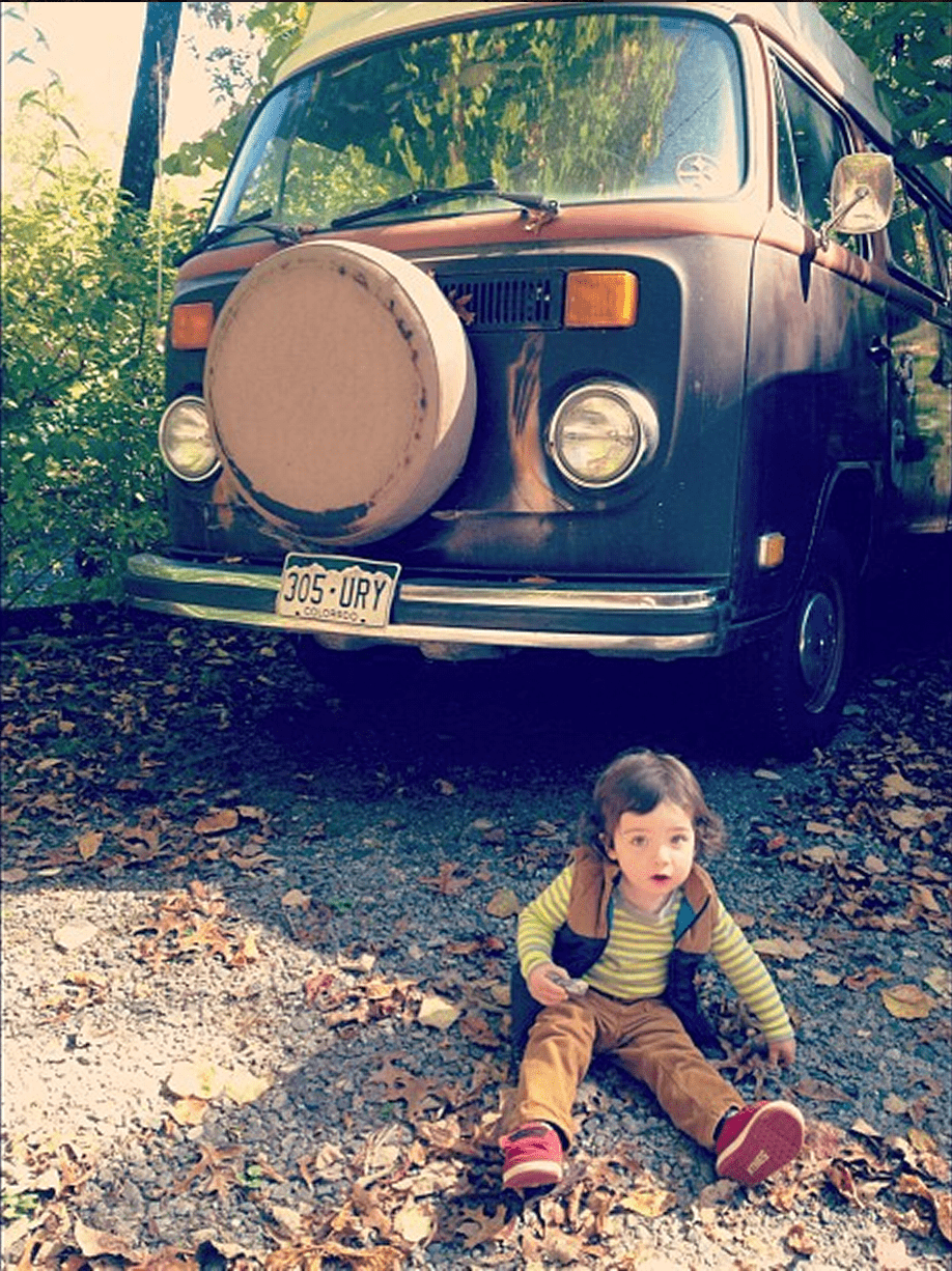 a toddler sits on the ground in front of a 1979 volkswagen bus