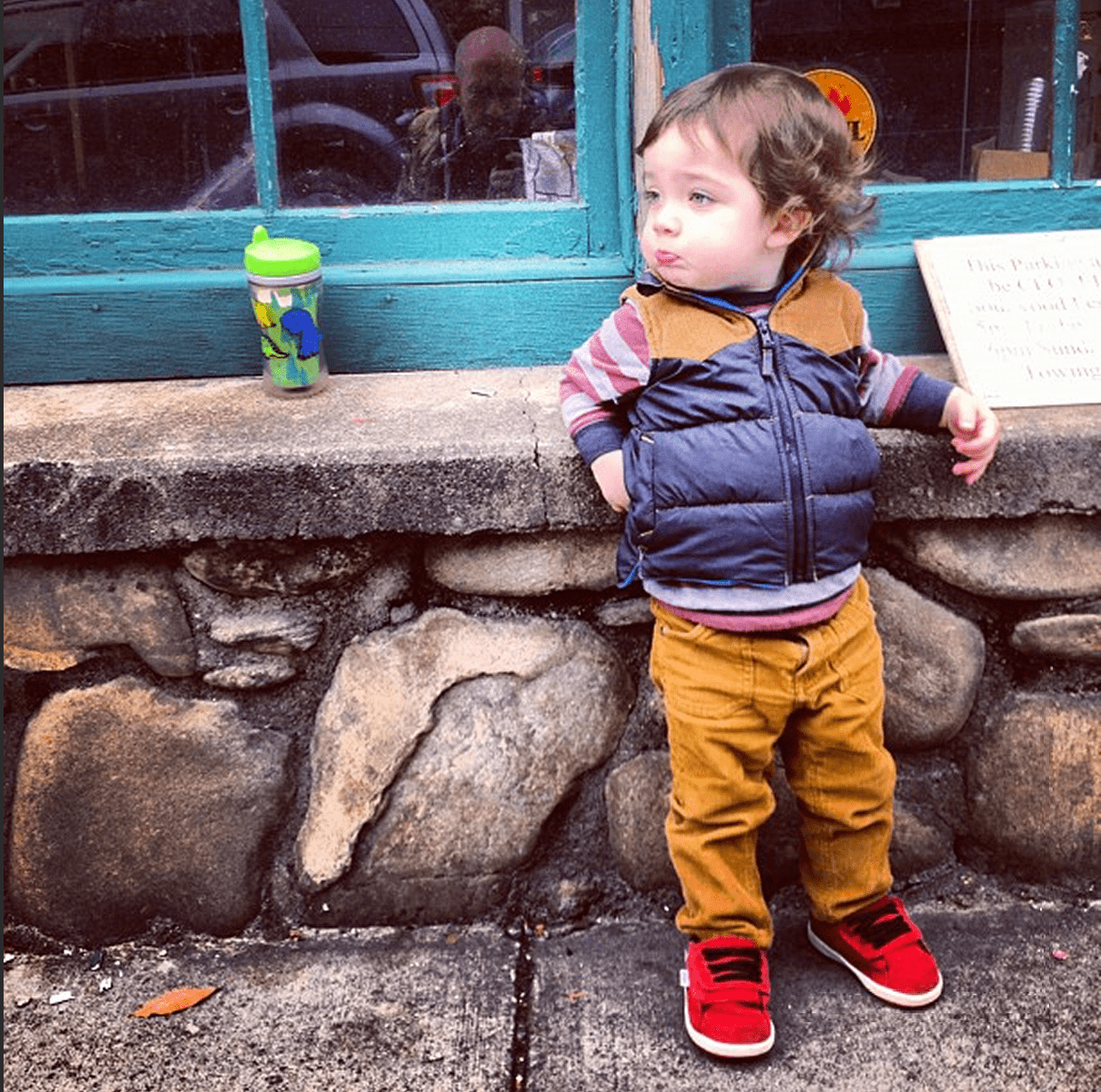 a toddler wearing a vest and brown corduroy pants kicks back against a stone wall