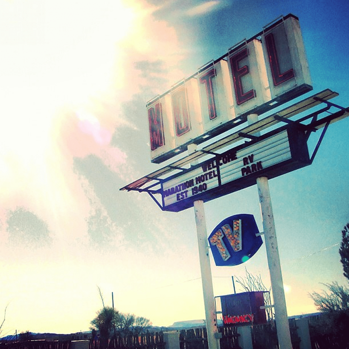 the sun blasts over a motel sign in the desert
