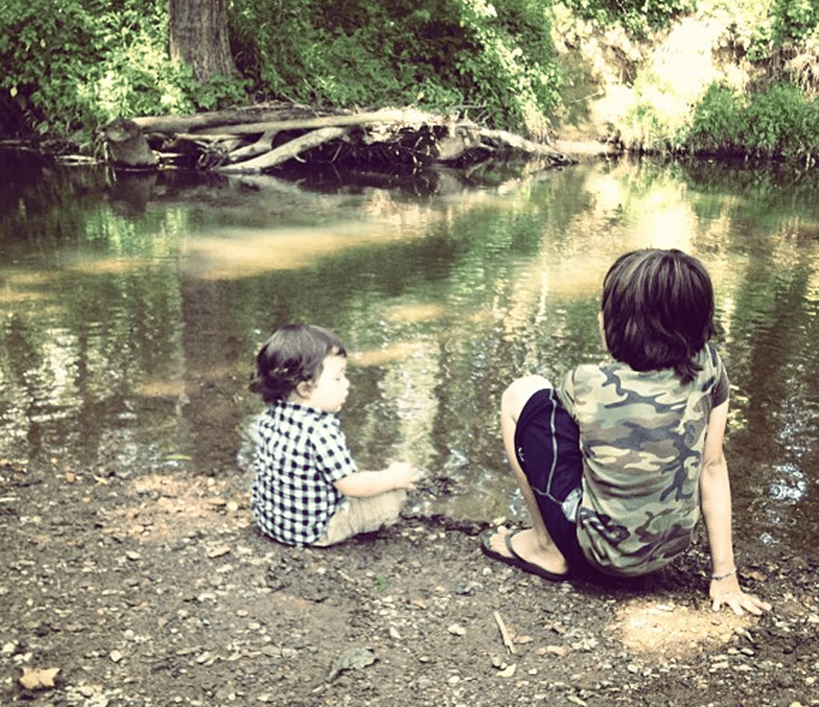 two young boys sit by a creek