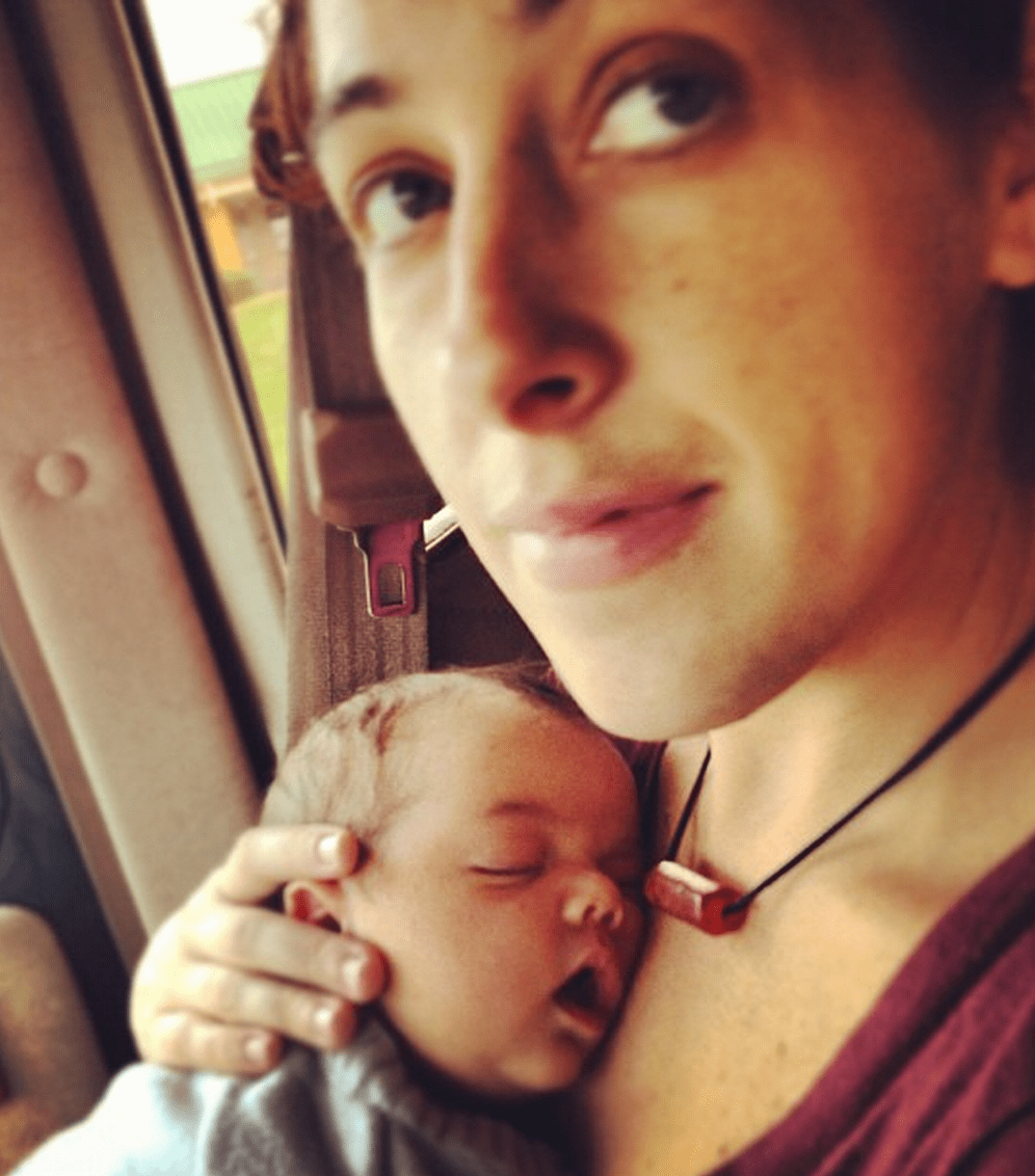 a mother holds her infant child in the front seat of a vw bus