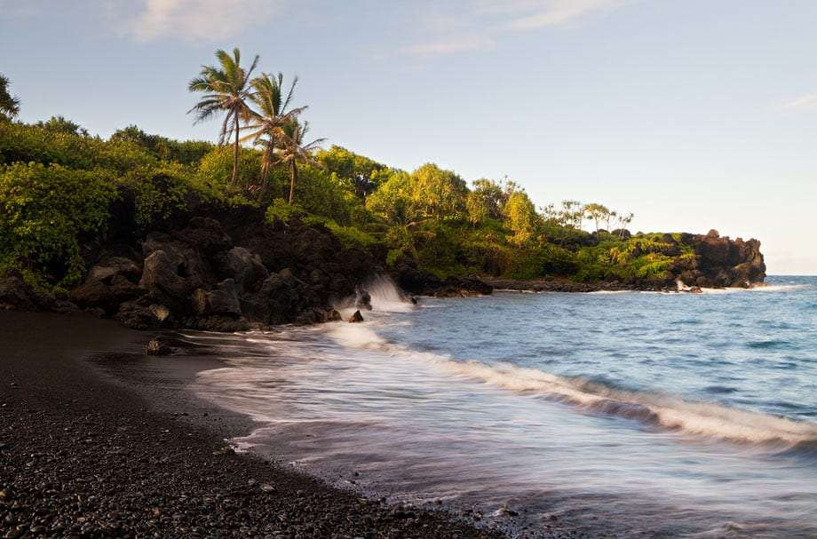 the beach off the road to Hana, lush and green foliage blossoms around