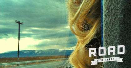 blonde hair looks out a moving car window, the open road and mountain beyond. plus roadtrippers logo