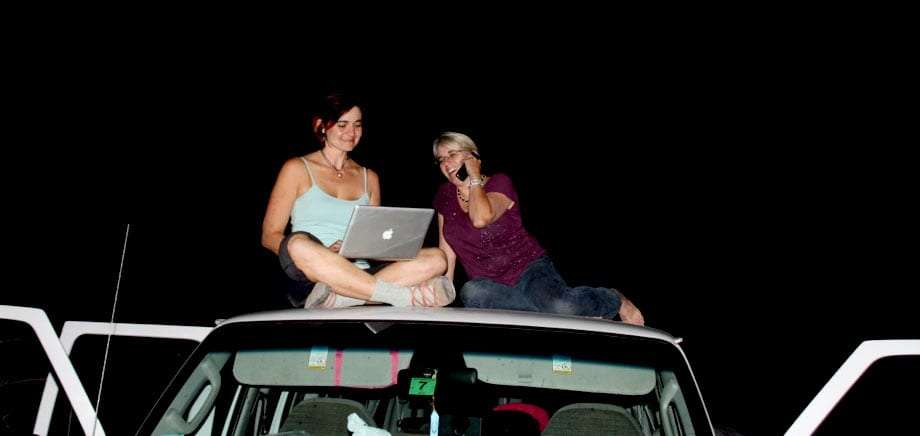 two women sit on the roof of a van, one talking on her cell phone, the other working on a macbook pro, beneath the night sky