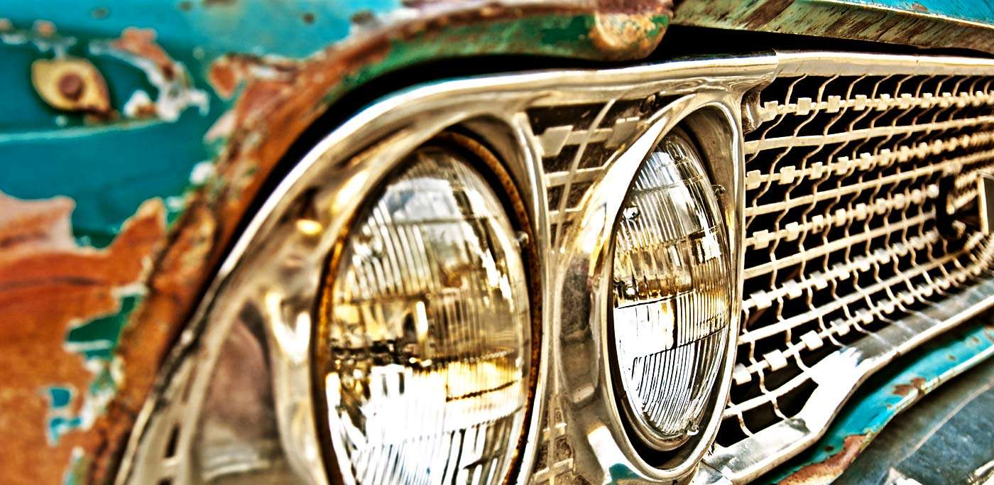 portion of the front grill of a turquoise, slightly rusted, vintage american car
