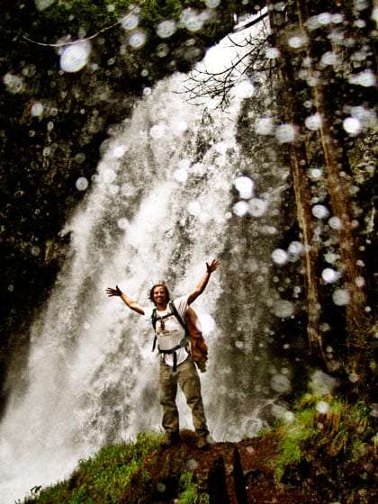 a backpacker stands at the foot of a waterfall, the camera lens is covered in water droplets