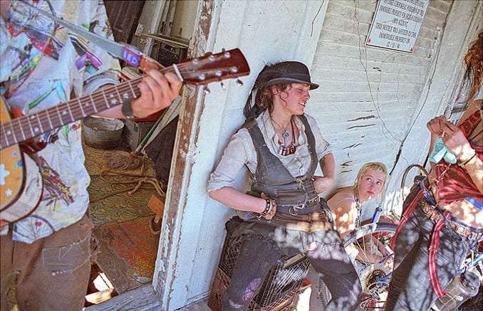 young women, wearing patchwork clothing and playing music, sit outside a dilapidated building
