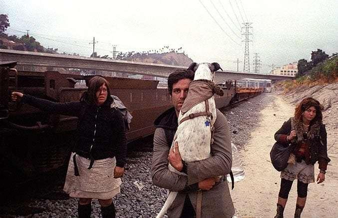 three train hoppers walking alongside the tracks, one carrying a dog