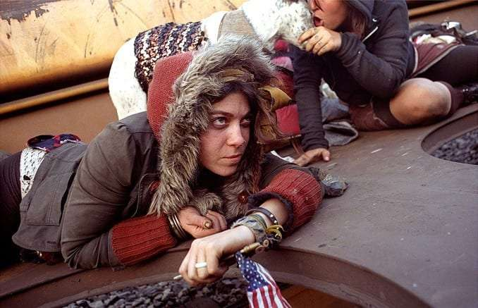 a young girl, dressed in a parka and holding an American flag, lies down in a train car