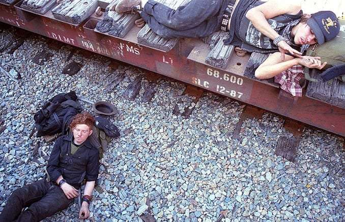 two young men sleep, one next to train tracks, the other on a flat car