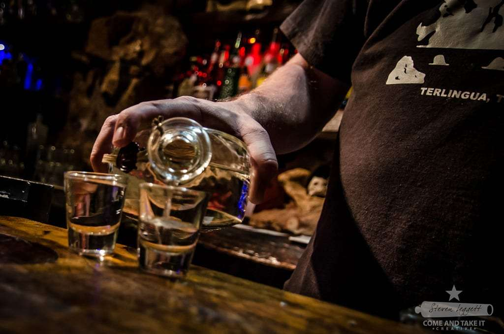 shots of whiskey being poured, the bartenders face can't be seen but his shirt reads Terlingua