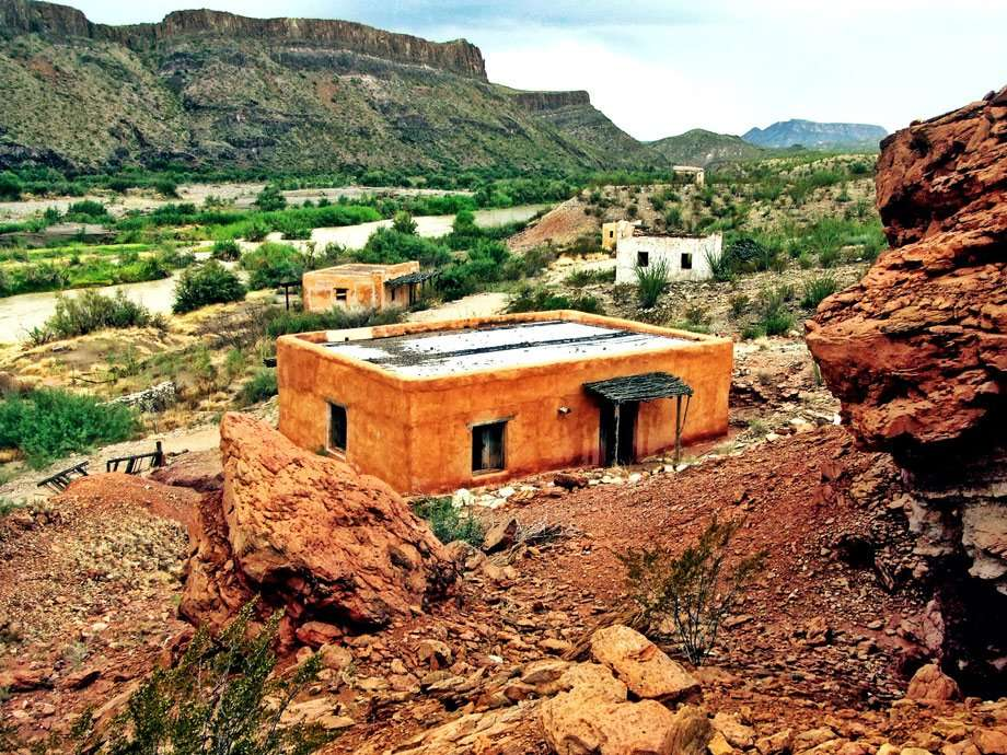 several adobe houses dot the landscape just north of the Rio Grande river's American bank